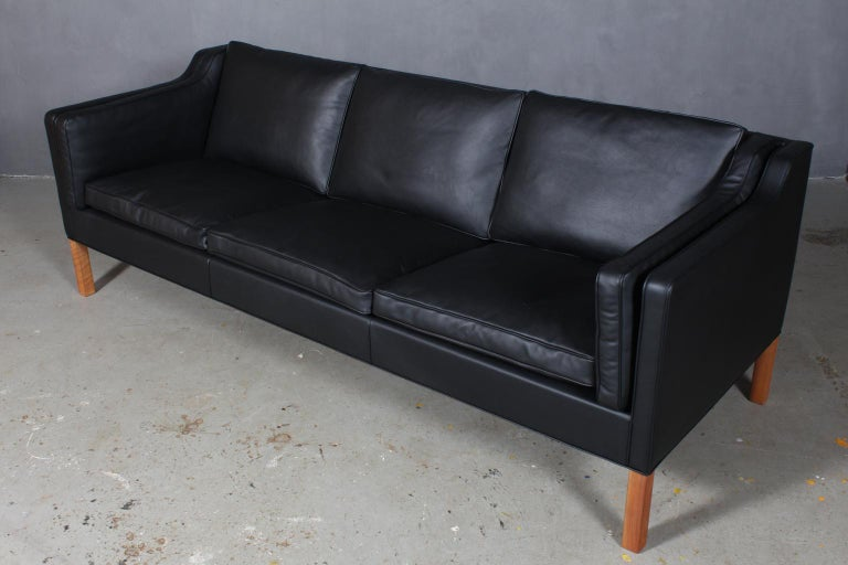 Børge Mogensen three-seat sofa new upholstered with black elegance aniline leather.  Legs of mahogany.  Model 2213, made by Fredericia Furniture.