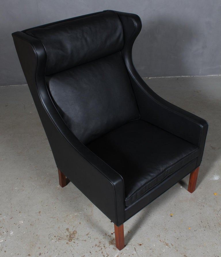 Børge Mogensen wingback chair new upholstered with black elegance leather.  Legs in teak.  Model 2204, made by Fredericia Furniture.