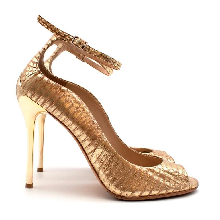 Brian Atwood Gold Snakeskin Embossed Open Toe Sandals  -Luxurious gold snakeskin  -Sculptural golden heel  -Peep toe design  -Ankle strap with buckle fastening  -Leather lining for comfort   Materials: Main- snakeskin  Lining-leather  Soles-leather