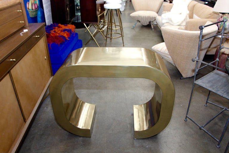 A pretty c shaped console by British over Time Originals. This is a unique one of a kind Prototype custom built. It is coated in Brass and Clear Coated. Designed by Bridges over Time and created by Marco Antonio.   A few minor dings which are