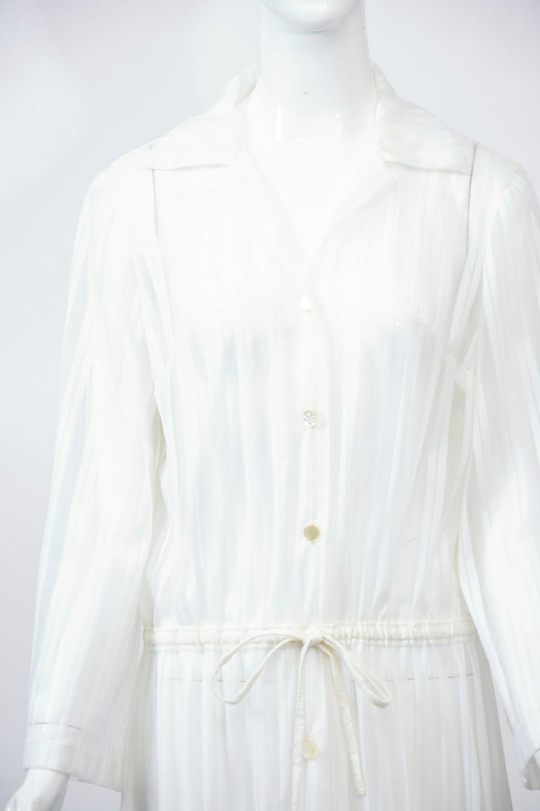 A long beach coverup, c.1970s, by Brigance in sheer white nylon with a vertical striped pattern. Button-down shirt style with drawstring waist.  Timeless. Size M.