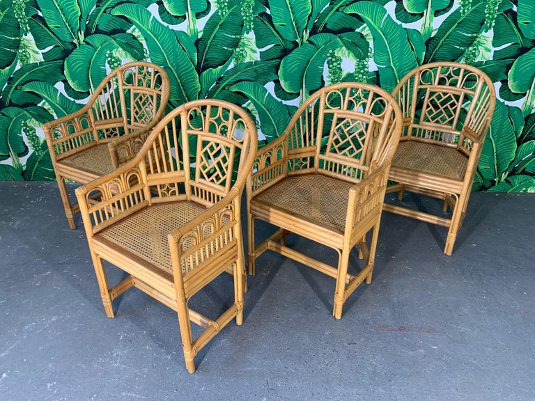 Set of 4 Brighton Pavilion style rattan dining armchairs feature bamboo construction, cane seats, and chinoiserie style detailing. Very good condition.