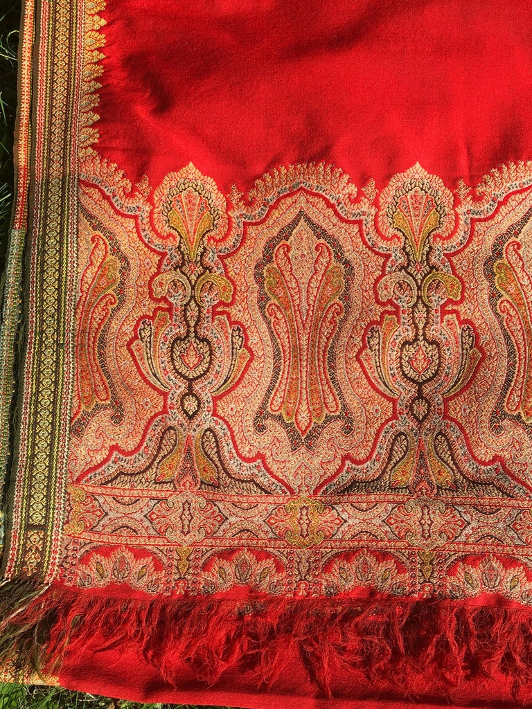 Brilliant tomato red finely woven wool Kashmiri throw or shawl with beautiful paisley borders. Predominantly red wool with red, yellow and green embroidered borders at the base and along the sides. Very large size throw. Few very small holes and