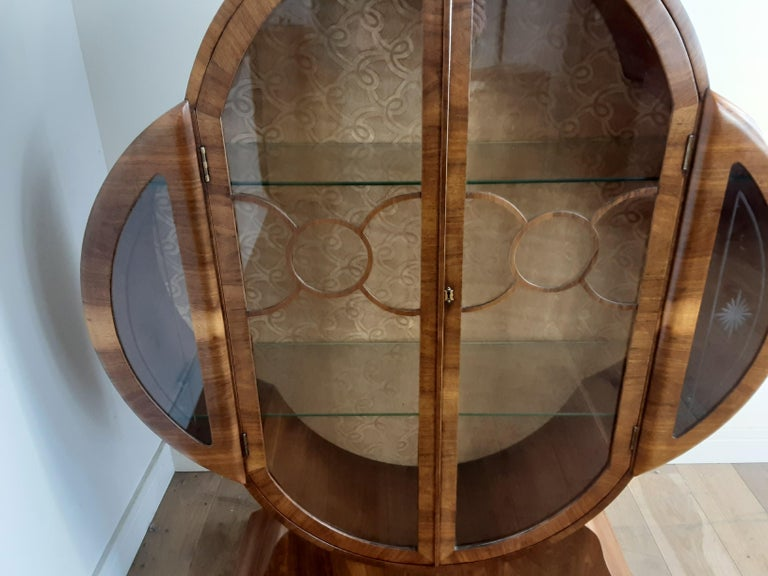 British Art Deco walnut display cabinet. Stunning and rare cloud shape display cabinet in a nice figured walnut with a circular fretwork design to the glass panel doors. British, circa 1930. Measures: 139 cm H, 120 cm W, 32 cm D.