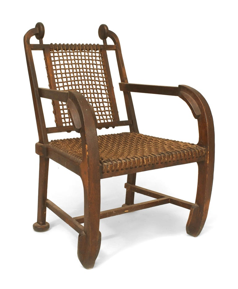 English (possibly Scottish) Arts & Crafts rustic design dark stained oak arm chair with nautical paddle form arms and legs with a woven rope seat and back.