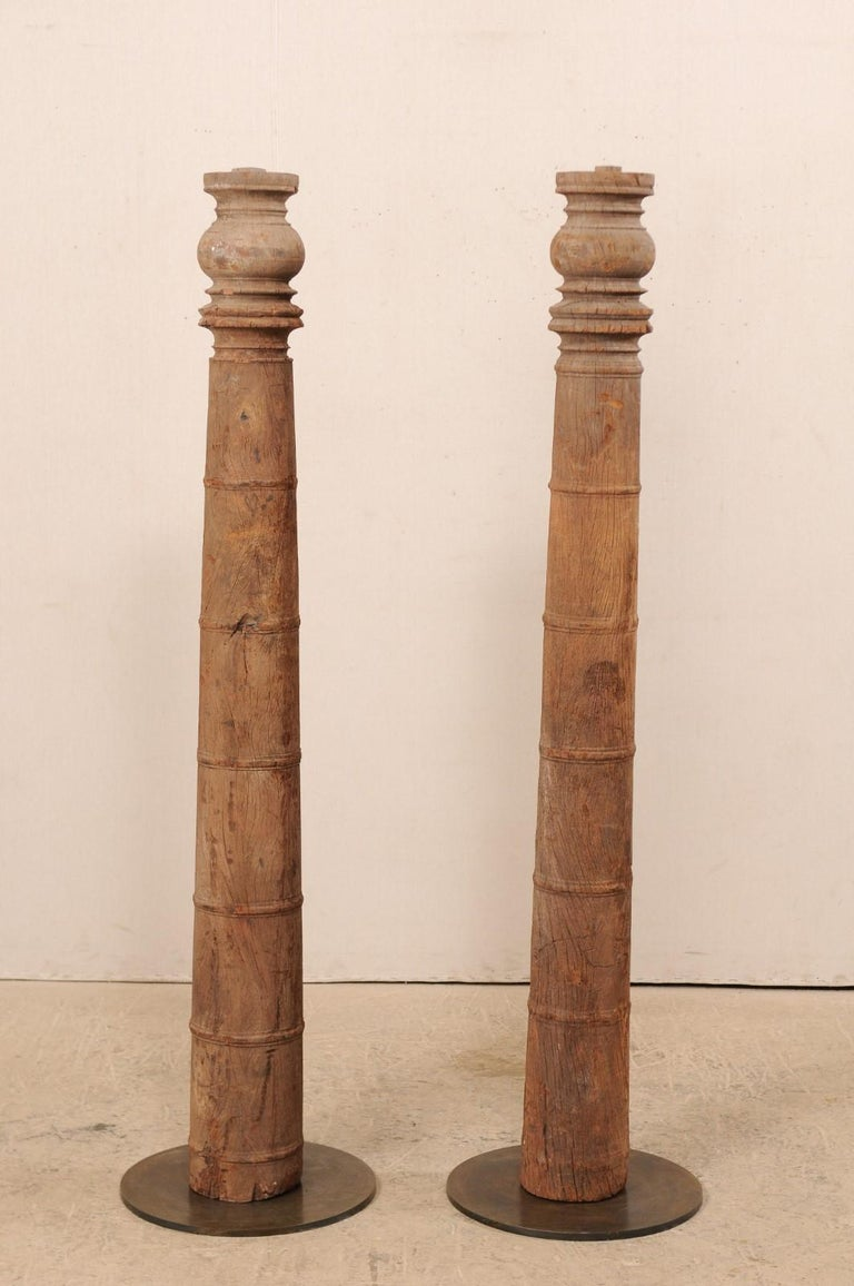 A pair of 19th century British Colonial carved wood columns on custom stands. This pair of antique hand carved wooden architectural elements from India, which stand approximately 5.5 feet in height, each feature a rounded column adorn with a series