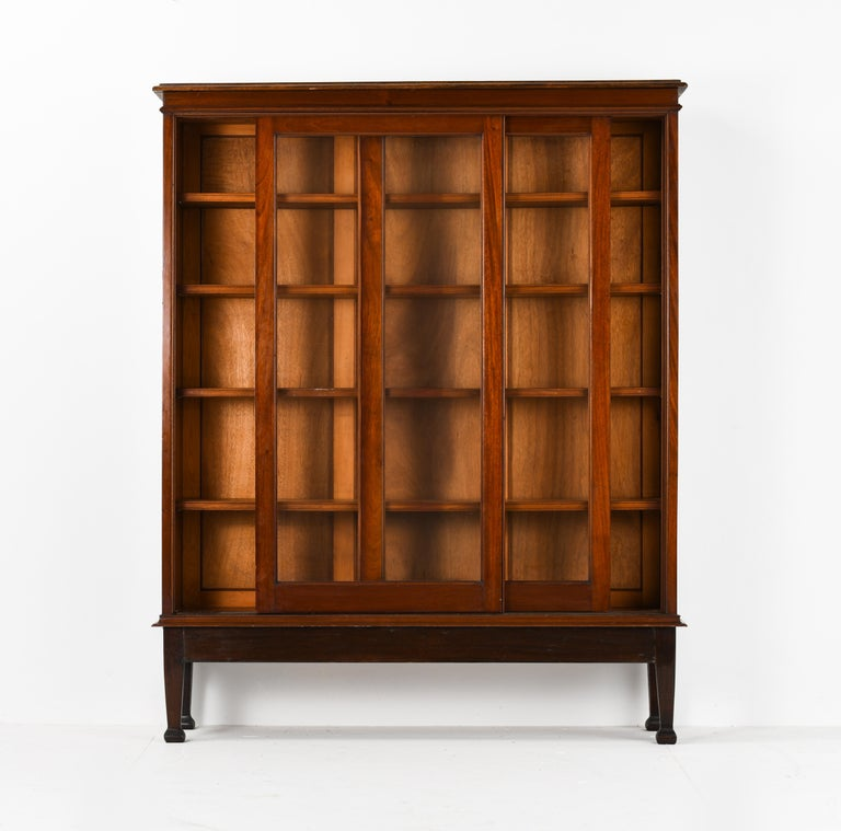 This handsome British Colonial bookcase with very good proportions it's made from Burmese teak and dates, circa 1950s. This bookcase features a set of sliding glass panel doors teak framed that open to compartments lined with 4 shelves and original