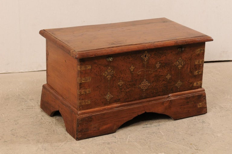 A British Colonial chest, which could function well as a small coffee table, from the early 20th century. This antique British Colonial keep-sake trunk of jack-wood is nicely adorn with a floral motif brass inlay pattern about it's front-facing