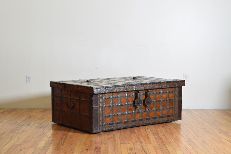 A large 19th century rectangular iron-bound wooden coffer box or Rajasthan trunk from British Colonial India with hinged top hatch.