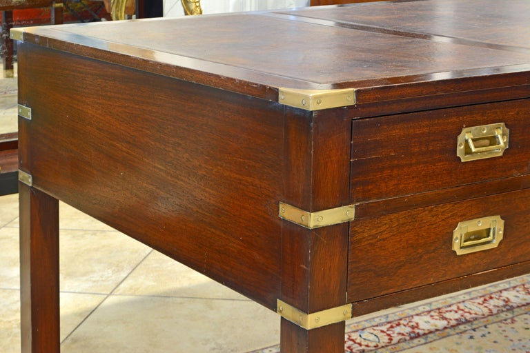 This British Colonial Mahogany campaign style desk features a top with three leather lined panels above five drawers with flush mounted brass handles on one side and simulated drawers on the other. The joints are accented by flush mounted brass