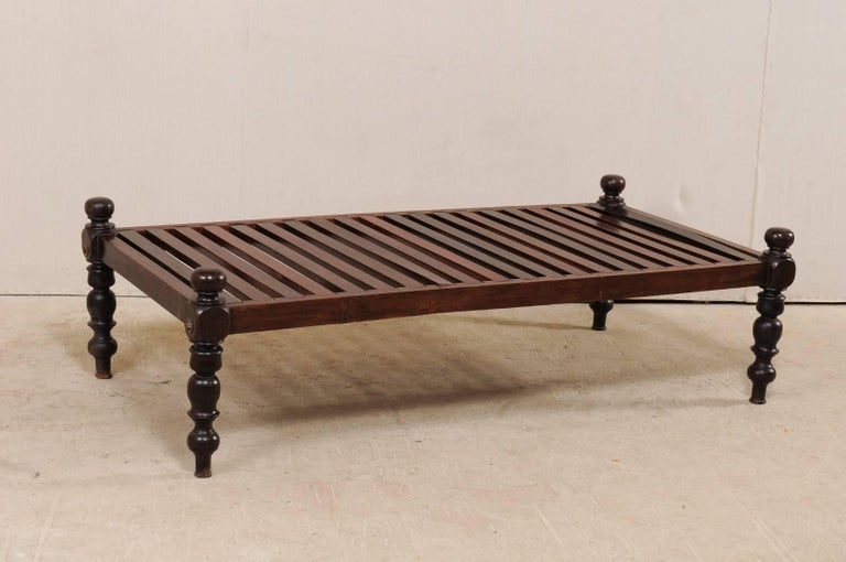 A British Colonial daybed from the mid-20th century. This vintage British Colonial style daybed from India features a sturdy wooden constructed slat bed, and four nicely turned legs, which rise slightly giving this bench low profile or open sides.