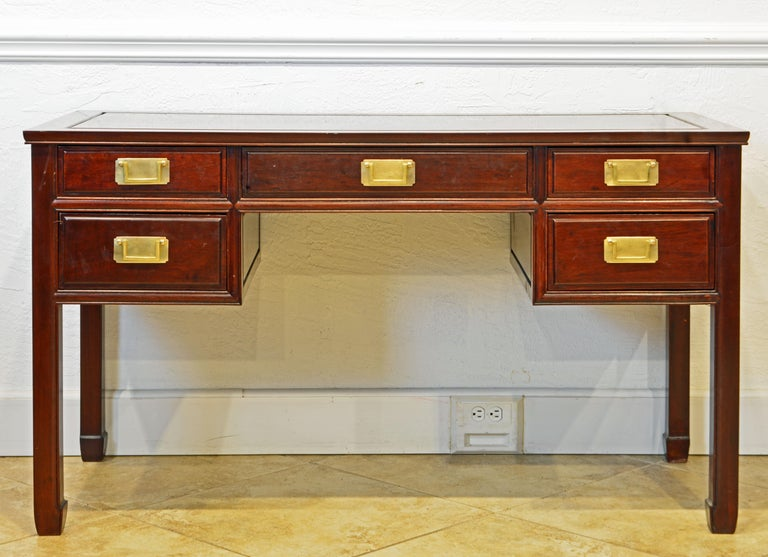This British Colonial style writing desk is made with great craftsmanship of solid polished mahogany, even the five drawers. It is likely to originate in Hong Kong dating to circa 1970. All surfaces are made as framed panels, even the top, which