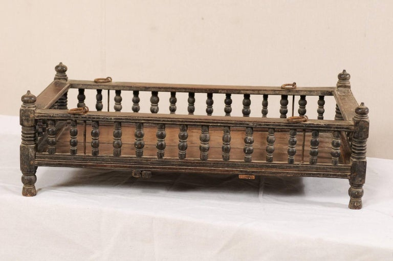 A British Colonial wooden pet bed from the mid-20th century. This vintage Anglo-Indian tropical hardwood piece originated as a baby's bassinet, with petite turned-baluster railing, and finials decorating each corner. The tropical hardwood is a dark