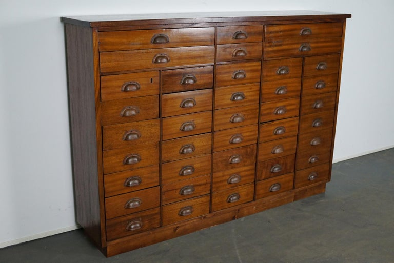 This vintage mahogany bank of drawers dates from the 1930s and was made in England. It features a solid wooden frame, the drawers are mahogany veneered with metal cup handles.