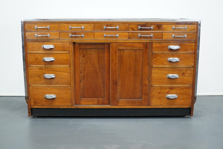 This vintage mahogany haberdashery shop counter with walnut veneer sides and palissander details dates from the 1930s and was made in England. It features a solid wooden frame and drawers in mahogany with art deco style handles.