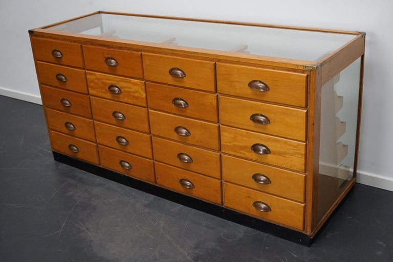 This vintage maple haberdashery shop counter dates from the 1930s and was made in England. It features a solid wooden frame with brass details, a glass casing and drawers in maple with copper handles.