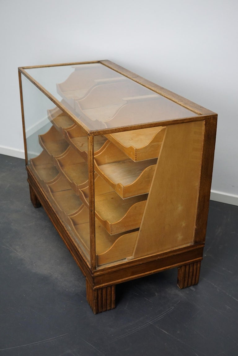This vintage oak haberdashery shop counter dates from the 1930s and was made in England. It features a solid wooden frame, a glass casing and drawers in oak with copper handles and brass name card holders.