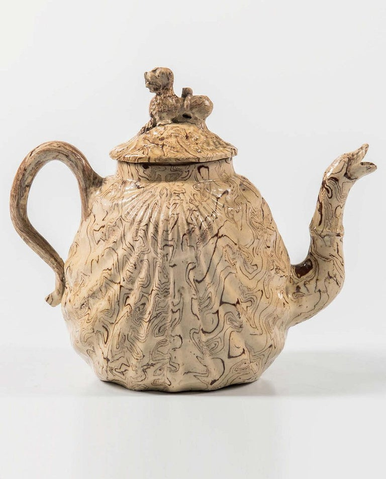 British Pottery solid agate Pecten shell teapot and cover, circa 1755-1760.  The lead-glazed light cream and red agateware pottery teapot is molded in the form of a pecten shell with a foo-dog finial and a serpent spout.  Dimensions: 5 3/4