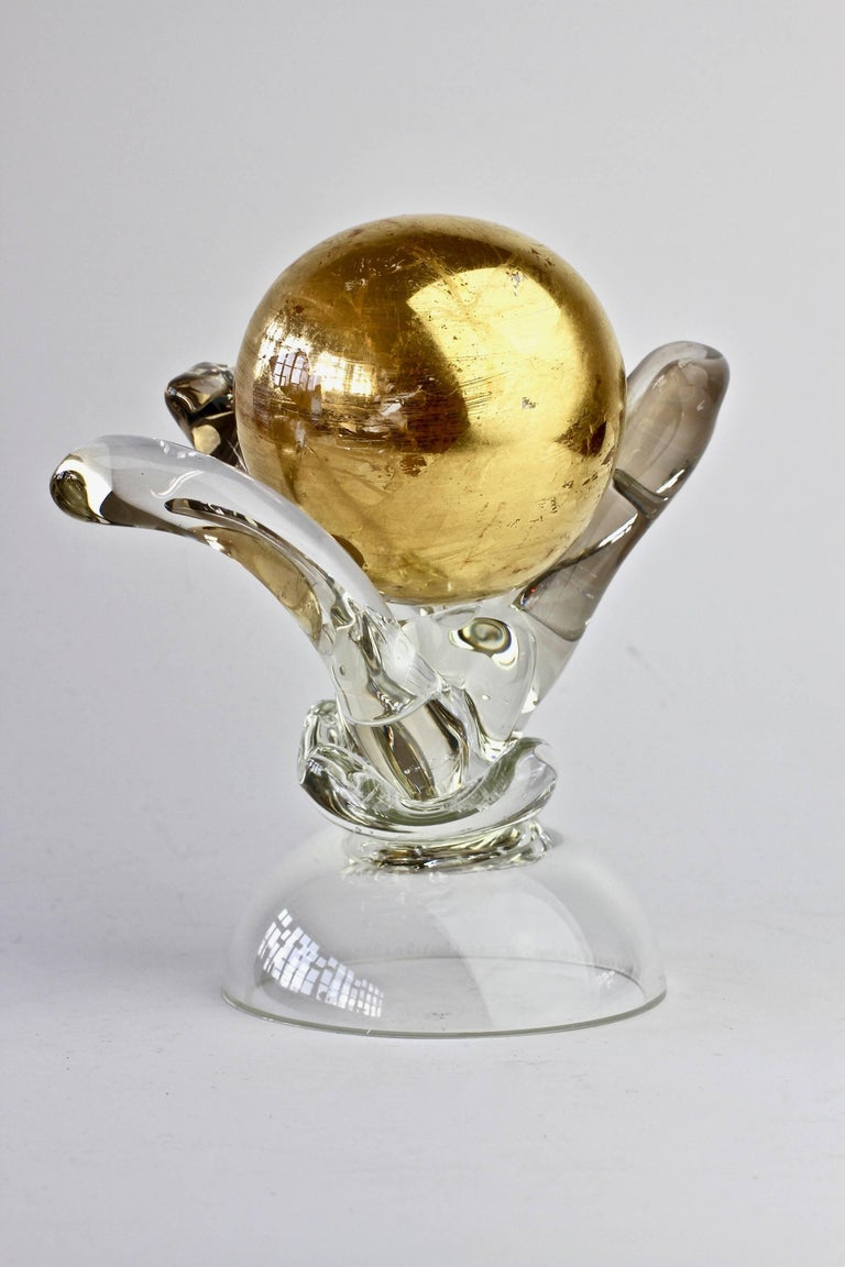 Unusual and quirky art glass sculpture signed by British glass artist and maker Adam Aaronson, England, 1997. Elegant and organically formed holding a 'golden globe' gilded glass ball.   This was produced 1997 - in the middle of Adam Aaronson's