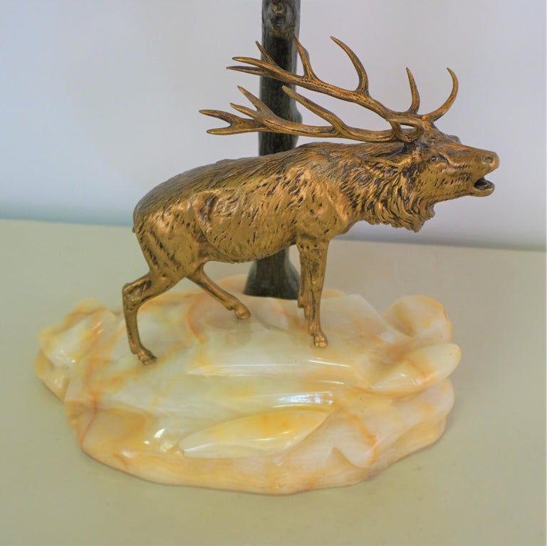 A fabulous desk lamp with golden bronze buck standing on piece of rock, dark green-black tree trunk as base that art glass shade rest on.