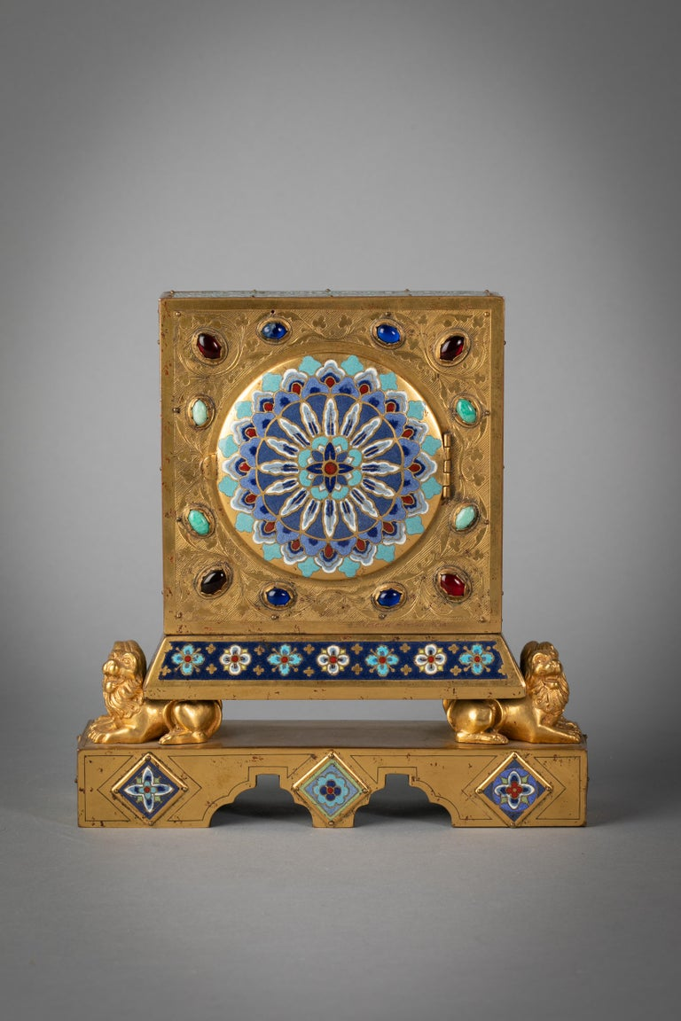 The face of the clock surrounded by eight applied panels (four round and four rectangular), All surmounted on the backs of four lions, above a platform with additional applied plaques, the back similarly decorated and studded with stones. Signed