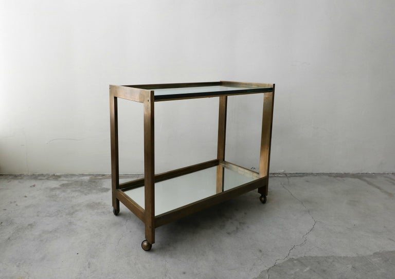 An entertainer's dream, simple yet sophisticated. A stunning, high quality bronze, glass and mirror midcentury bar car. The transparency of this piece makes it perfect in most any space. With two tiers, the top one glass and the bottom one mirror.