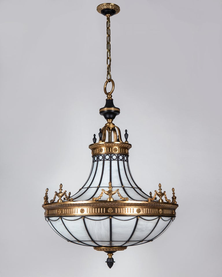 AHL3554  A large antique leaded glass chandelier with bronze framing in a combination of dark and bright-burnished finishes. The metalwork is detailed with twin friezes of leaf-and-dart moldings over rosettes and fluting. Each molding topped with