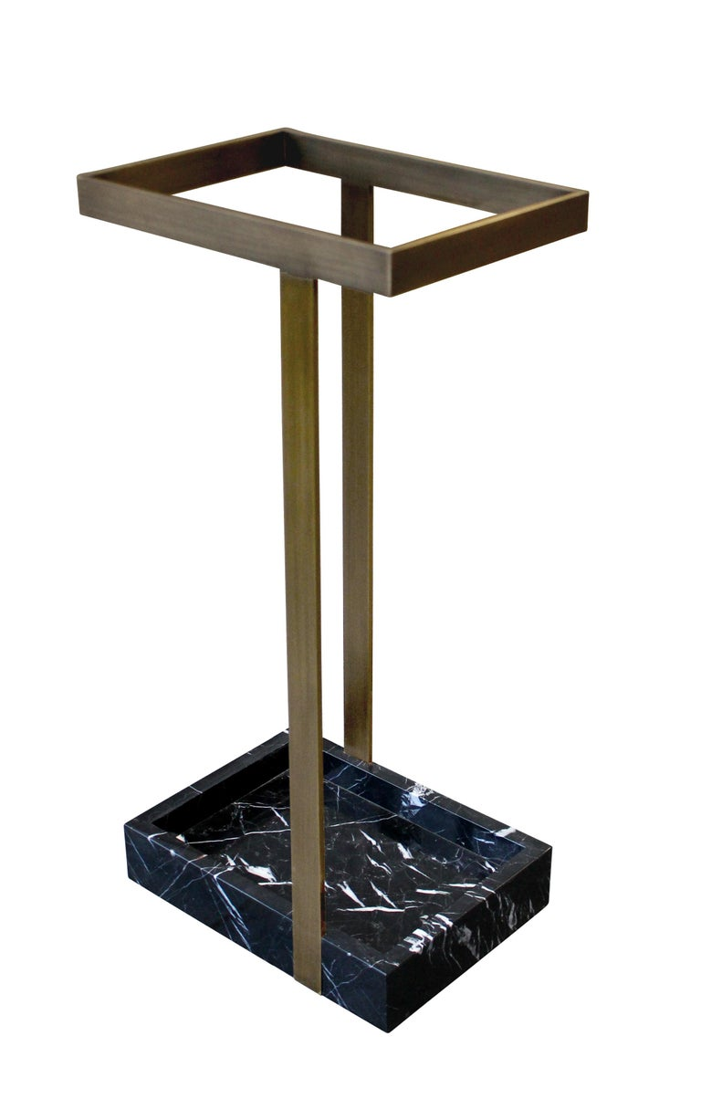 This subtle yet striking umbrella stand creates an arresting focal point in a foyer or vestibule. Shown here in patinated bronze with nero marquina marble, the piece is handmade to order in New York City and can be specified in any number of custom