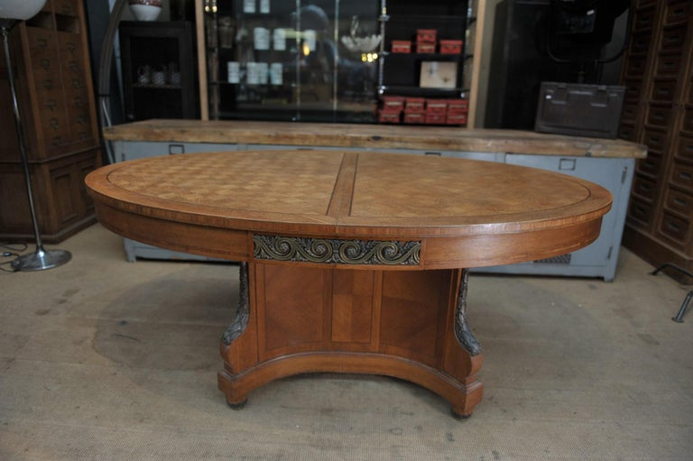 Great Quality Louis XVI style dining oval table in oak marqueterie and bronze ornament with central base and 2 set of feet folding with metal système when open. 5 long 80 cm (31 inches) wood sliding parts can be use for 2 to 5 extensions, that we