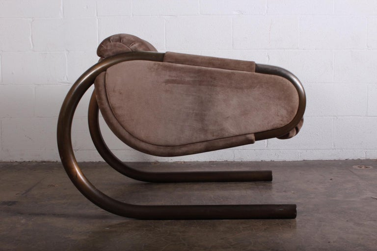 A large scale lounge chair with bronze plated frame and suede upholstery by Dunbar.