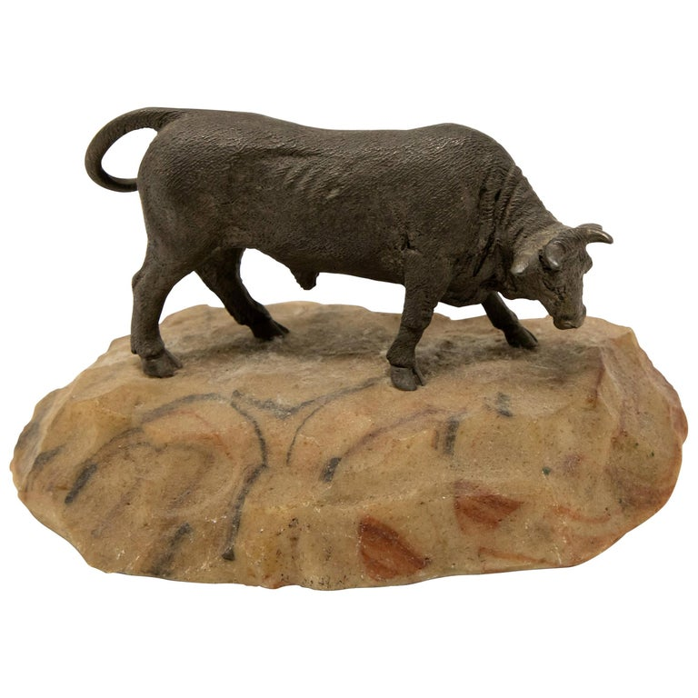 Offering this sculpture of a bronze bull on stone base. Starting with the base is a sand colored stone with some airbrushed reds and blacks. Mounted is the bronze bull with his tail swinging and head down.
