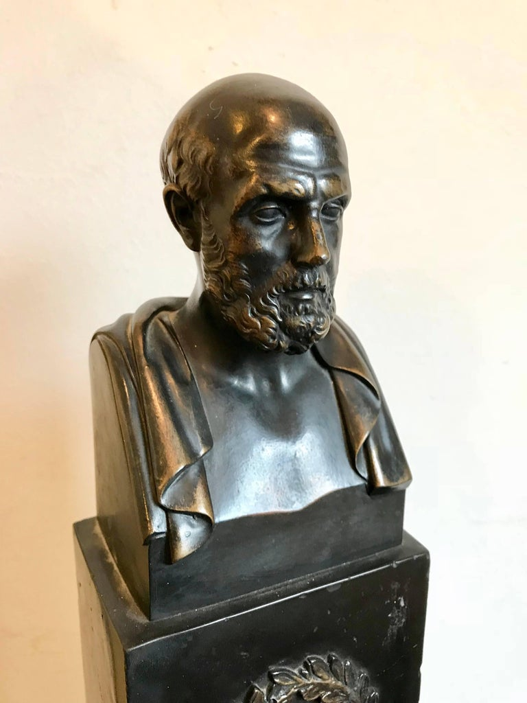 High quality Grand Tour bronze bust of Hippocrates depicting the bearded Greek god on a faux marble scagliola plinth. Modeled after the ancient Roman marble original. The black stepped base with a laurel wreath in relief. 