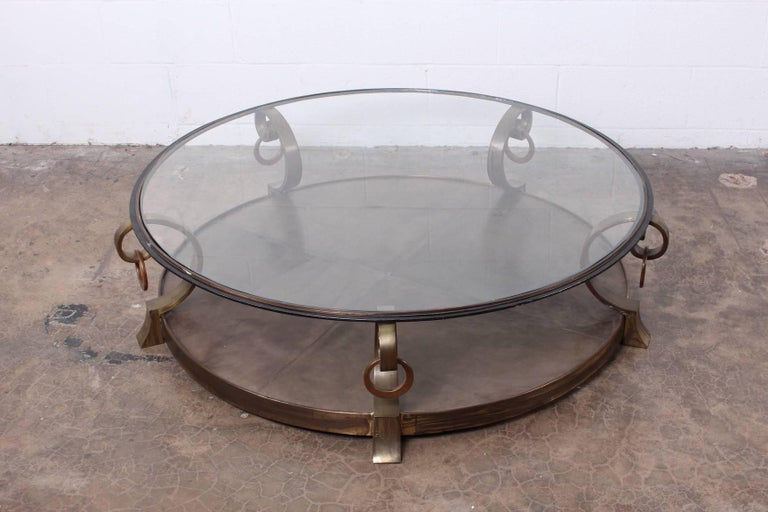 A bronze coffee table with leather inset and glass top. Designed by Arturo Pani.