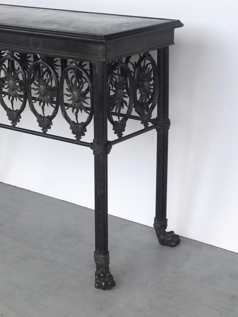 A bronze console table with sun and lion's paw motif.