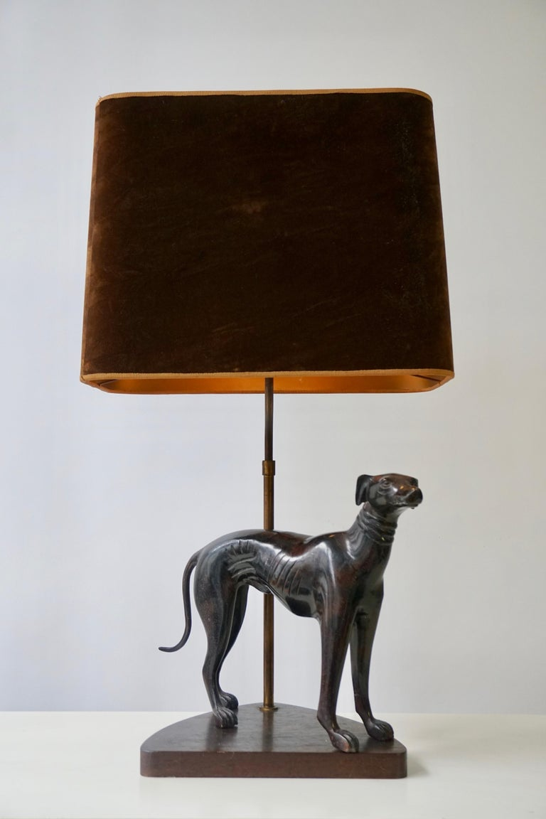 A charming table lamp with a bronze dog created at the middle of the 20th century, standing on an aged, wooden pedestal. Wired as a lamp with a slender, tinted brass stem. Height 71 cm. Width 40 cm. Depth 26 cm.