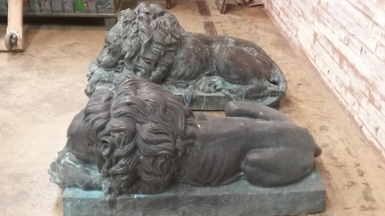 Great pair of bronze laying lions. A reproduction late 20th century pair that depicts both lions sleeping. A left and a right. Each is different. Acquired from upstate Connecticut estate. Originally made in Thailand. Very good condition with Verde
