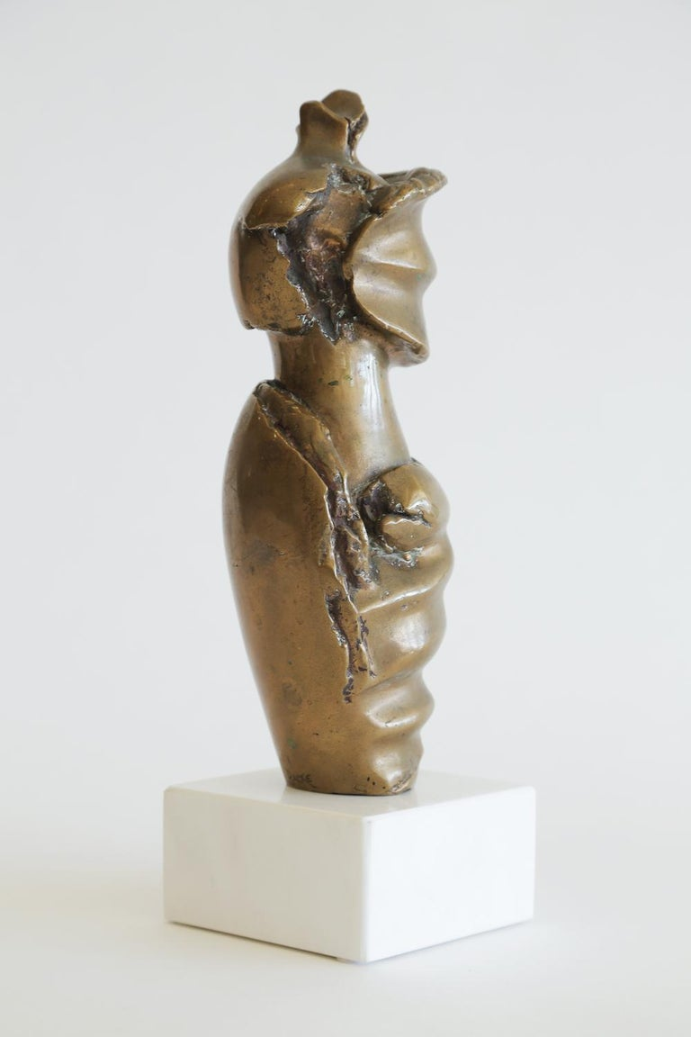 This sensual vintage bronze sculpture changes form with every movement and turn. It is a headless female draped women in bronze that is part Brutalist, part Egyptian Revival and part Mid-Century Modern. It has a white marble base. It is signed Backe
