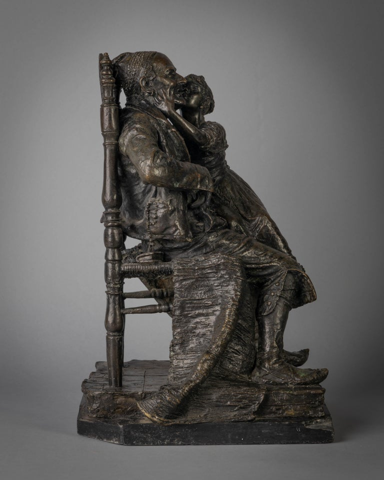 After a model by Constantino Barbella, late 19th century. The old man seated in a chair with the girl on his lap about to bestow him with a kiss, on a shaped square base. marked C. BARBELLA and it is signed in the mold C. Barbella Roma; the marble