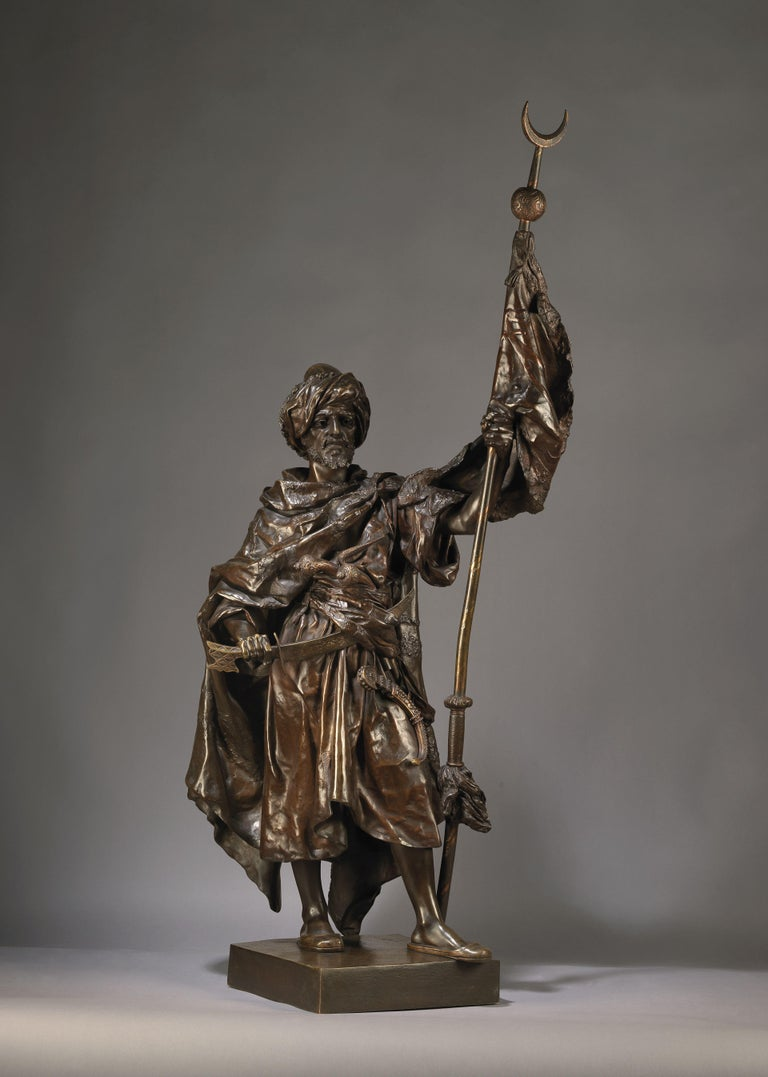 A large and important multi-patinated bronze figure of an Arab Warrior by Henri Honoré Plé.  French, circa 1880.   Signed Henri Plé to the base.   The figure is finely modelled as an Arab warrior, with sword drawn and crescent tipped standard