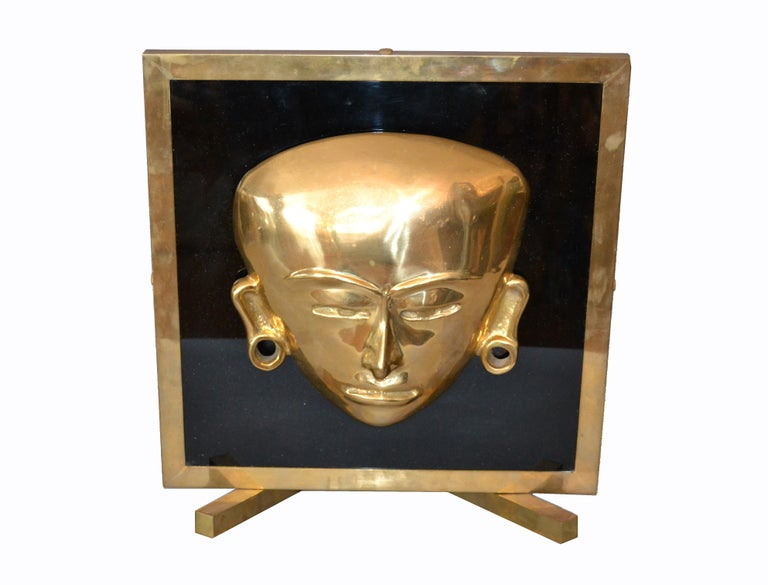 Decorative bronze framed brass African mask on black glass table art. No markings. It is very heavy and shows a warm patina.