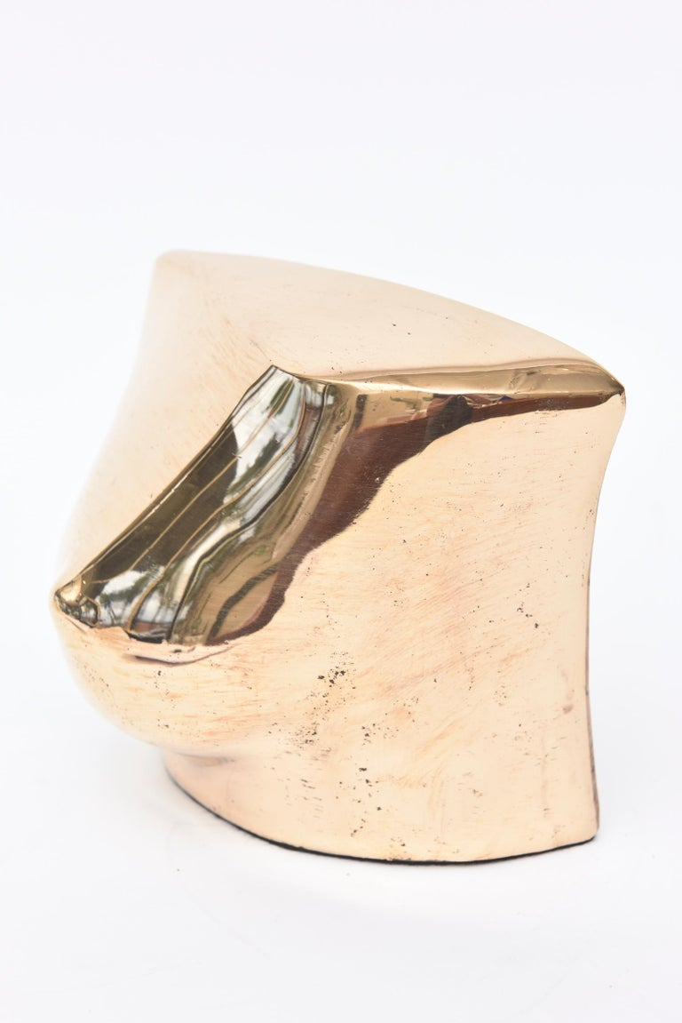 This wonderful cast bronze French abstract sculpture is a single breast. It is signed and numbered 100. It has been professionally polished. This makes a great tabletop sculpture or a great desk accessory that will elicit conversation to some