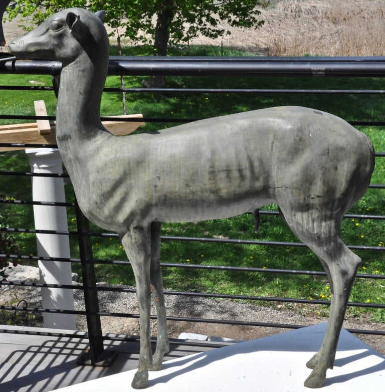 A realistic patinated bronze sculpture of a deer, copying the famous deer of Pompeii, late 19th century.