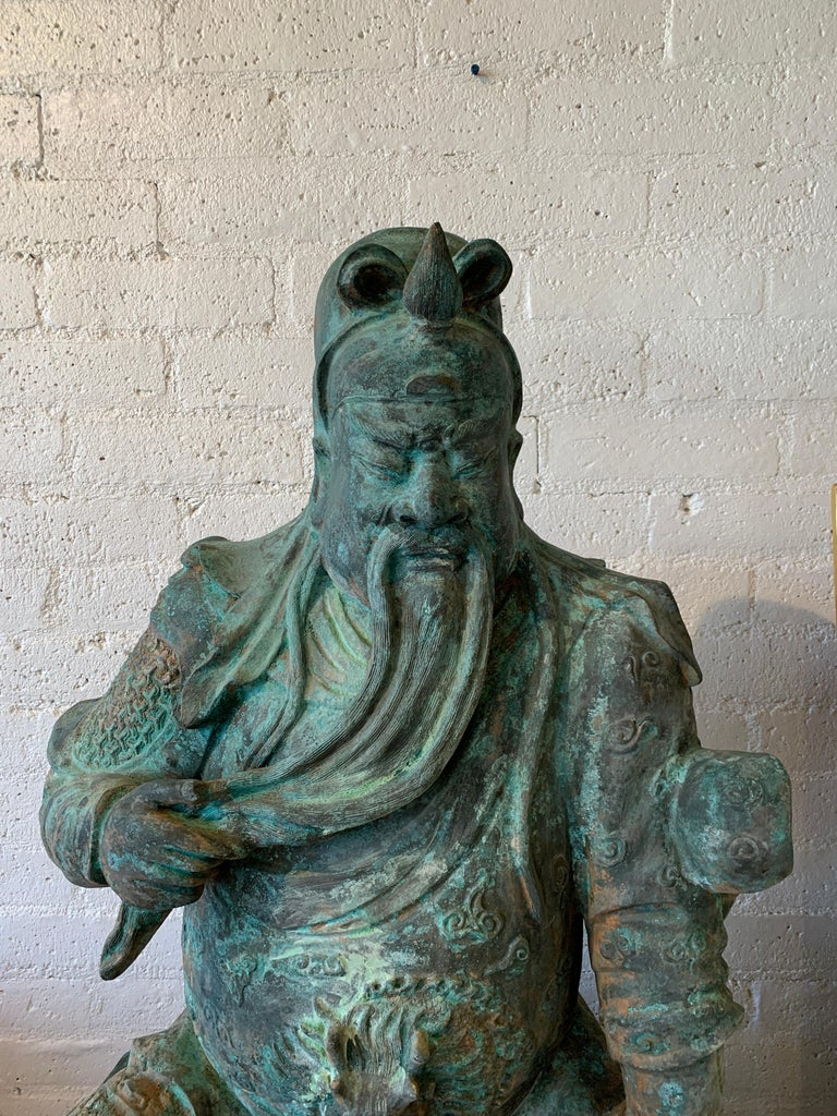 A massive larger than life size bronze seated figure of Guan Yu one of the most documented figures in Asian history. It has been sitting in a garden and has fabulous greenish patina. Nice detail and scale. In good condition with some imperfections
