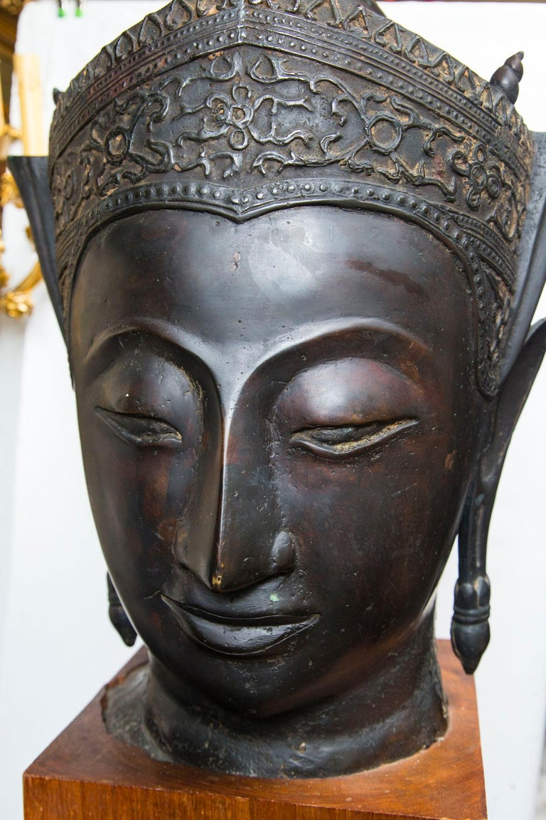 In the Thai style, with dark brown patina. Attached to a wooden block base. The head, itself is 24 inches tall. The base measures 10 x 10 x 9.5 tall.