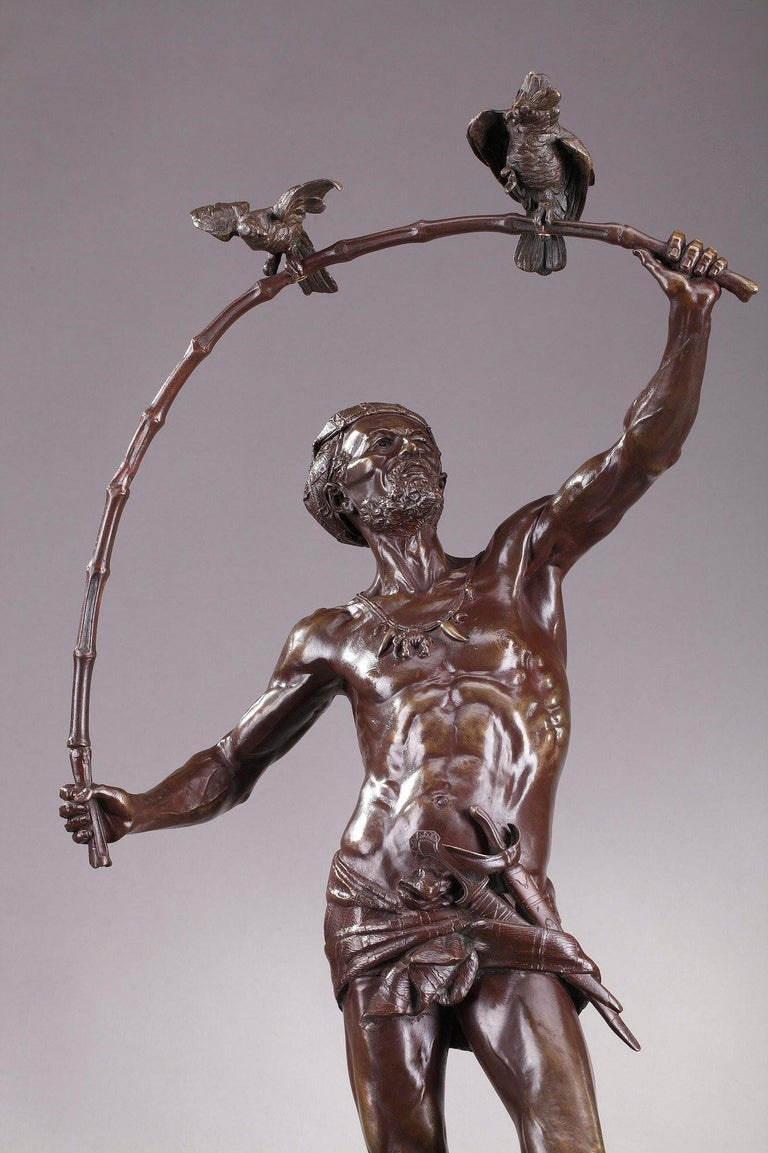 Large bronze statue featuring a Hindu bird-catcher by the Belgian sculptor and medallist Auguste de Wever. He wears a ribbon and a drapery supporting a small sword. His necklace is adorned with an elephant-shaped medallion. Our bird-catcher