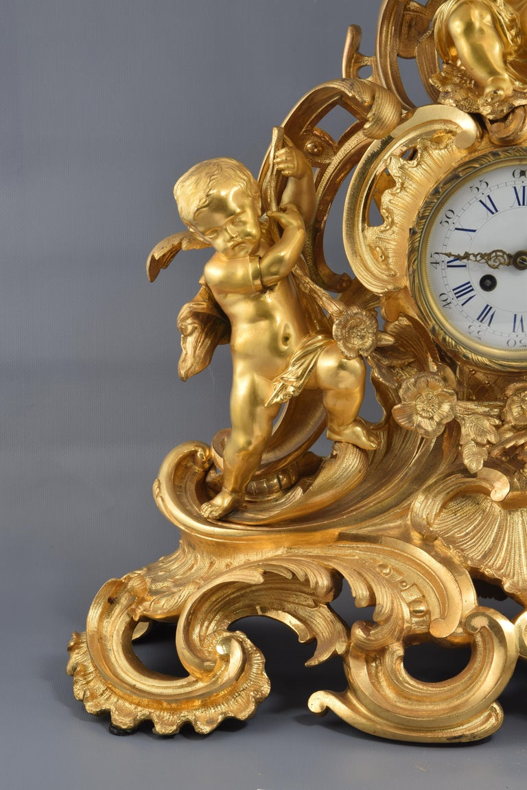 Table clock. Bronze, 19th century. Table clock made of gilt bronze featuring a white dial with Roman numerals for the hours and Arabic numerals every five for the minutes, Louis XV hands and a golden frame around. On a base that combines pebbles