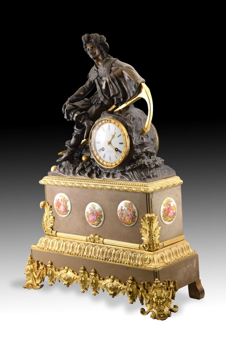 Table clock. Marble and bronze, 19th century.  Table clock with Paris box machinery made of marble and bronze and with porcelain plates applications with rococo souvenir scenes. The white dial features an inscription (Hoffman Fres. / Rues des
