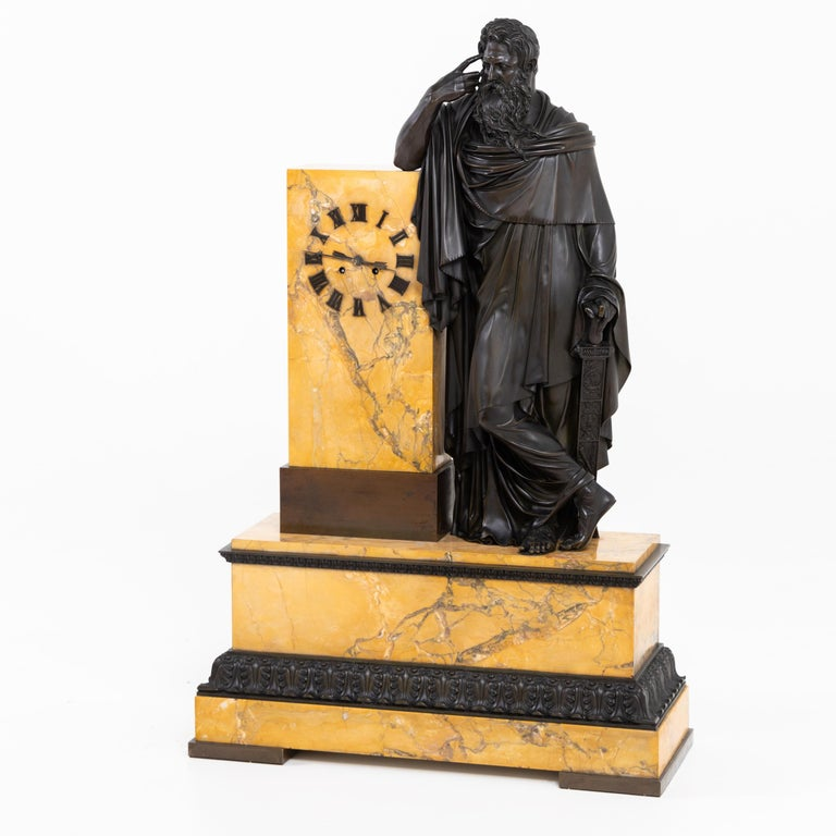The large pendulum on a Sienese marble base with patinated bronze frieze as well as large fully sculpted depiction of a bearded man with the index finger at his temple. The other hand rests loosely on the pommel of a sword. The movement is inscribed