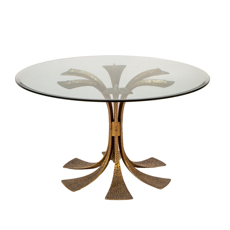 Bronze dining table by Frigerio. Round glass top on heavily detailed base.