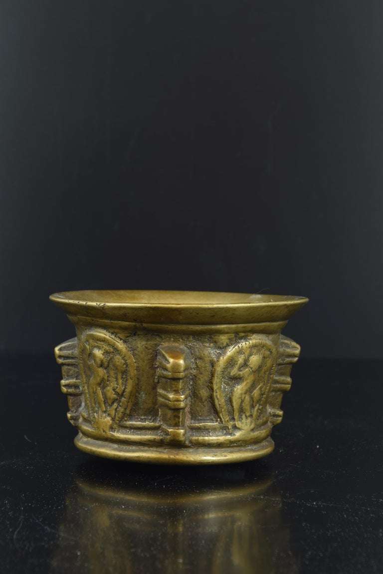 Mortar in bronze of the 17th century, decorated with ribs in the form of pillared pilasters and, in the planes, cartouches with the representation of Saint Michael the Archangel in relief. Size: 7 x 7 x 12 cms.